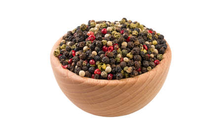 colored pepper peppercorns in wooden bowl isolated on white background. 45 degree view. Spices and food ingredients.