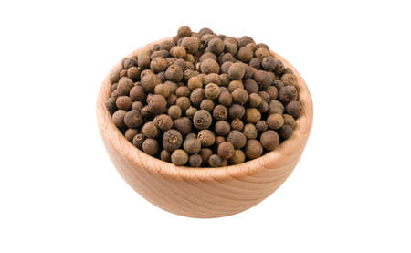 allspice or Jamaican pepper in wooden bowl isolated on white background. 45 degree view. Spices and food ingredients. Stock Photo