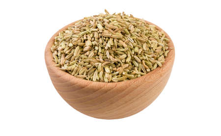 fennel seeds in wooden bowl isolated on white background. 45 degree view. Spices and food ingredients.