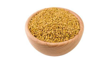 nasiona kozieradki w drewnianej misce na białym tle. Widok 45 stopni. Przyprawy i składniki żywności.
