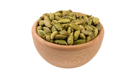 cardamon seeds in wooden bowl isolated on white background. 45 degree view. Spices and food ingredients.