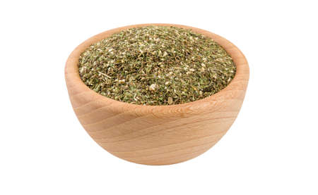 green savory mix or Chubritsa in wooden bowl isolated on white background. 45 degree view. Spices and food ingredients. Stock Photo
