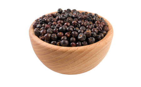 juniper berries in wooden bowl isolated on white background. 45 degree view. Spices and food ingredients. Stock Photo