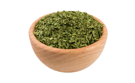 coriander leaves in wooden bowl isolated on white background. 45 degree view. Spices and food ingredients.