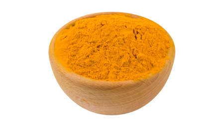 turmeric powder in wooden bowl isolated on white background. 45 degree view. Spices and food ingredients.