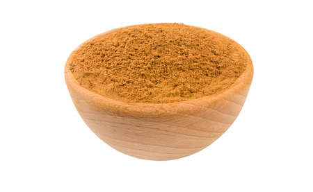 ground or milled cinnamon in wooden bowl isolated on white background. 45 degree view. Spices and food ingredients.