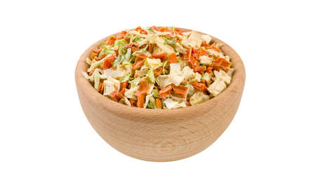 dried vegetables or soup vegetables in wooden bowl isolated on white background. 45 degree view. Spices and food ingredients.