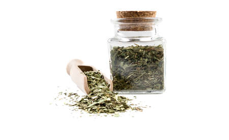 tarragon herb in wooden scoop and jar on isolated on white background. front view. spices and food ingredients. Stock Photo