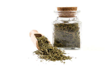 dill in wooden scoop and jar on isolated on white background. front view. spices and food ingredients.