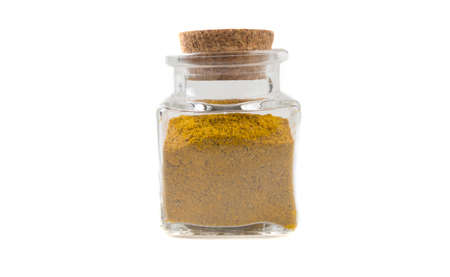 yellow curry in glass  jar on isolated on white background. front view. spices and food ingredients.