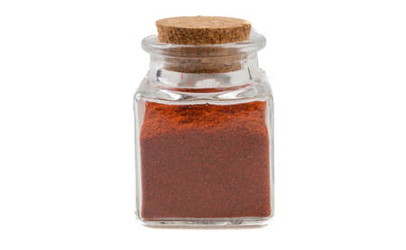 milled or ground paprika or red pepper in glass  jar on isolated on white background. front view. spices and food ingredients. Stock Photo