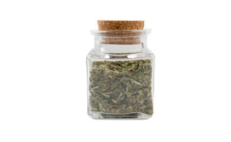 tarragon herb in glass  jar on isolated on white background. front view. spices and food ingredients. Stock Photo