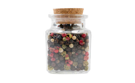 colored pepper peppercorns in glass  jar on isolated on white background. front view. spices and food ingredients.