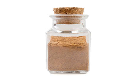 milled or ground nutmeg in glass  jar on isolated on white background. front view. spices and food ingredients.