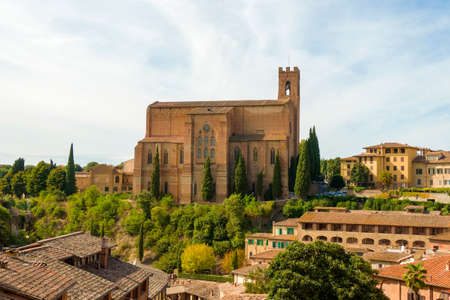 Scenic view of Siena cityscape over rooftops with San Domenico Basilica on background against blue sky. Tuscany, Italy 免版税图像