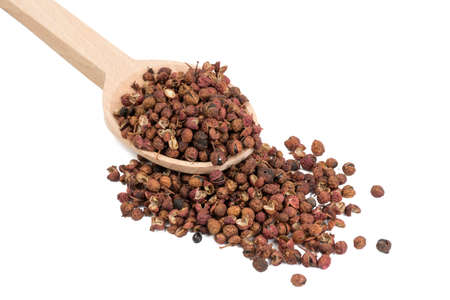 sichuan pepper in wooden spoon isolated on white background. food ingredient. Stock Photo