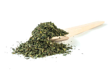 dried nettle herb or in latin Utricae folium in wooden spoon isolated on white background. medicinal healing herbs. herbal medicine. alternative medicine