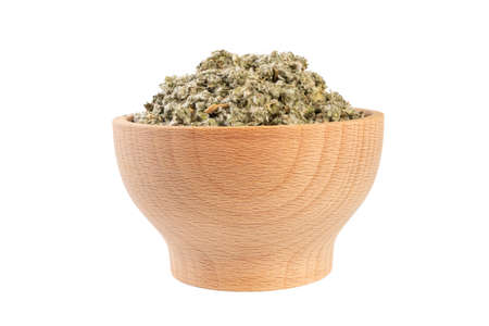 dried artichoke leaves or in latin Cynarae folium in wooden bowl isolated on white background. medicinal healing herbs. herbal medicine. alternative medicine