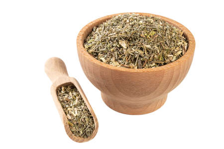 wormwood herb or in latin Absinthii herba herb in wooden bowl and scoop isolated on white background. medicinal healing herbs. herbal medicine. alternative medicine