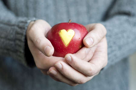 a red apple with a heart mark in man