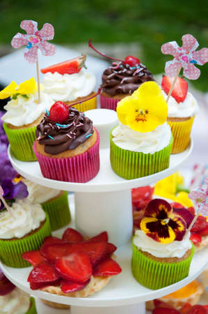 multicolored summer cupcakes with fruit and flowers photo