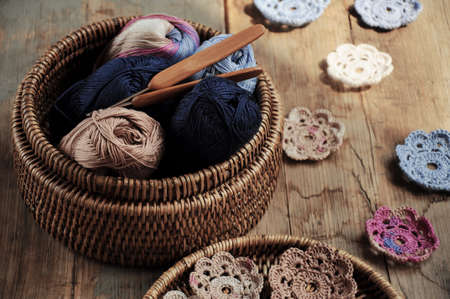 Box of yarn and handmade crocheted flowers Stockfoto