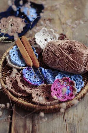 Box of yarn and handmade crocheted flowers photo