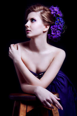 Elegant young blonde woman in a violet dress on the black background photo