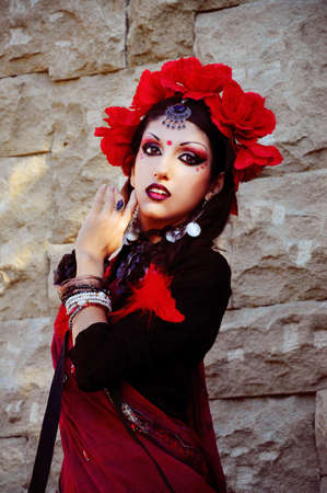 Indian woman with dramatic  makeup dressed in red sari photo