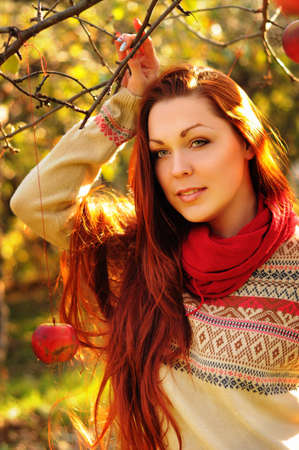 fellings: Young redheaded woman with long straight hair in the apple garden picking up the apples