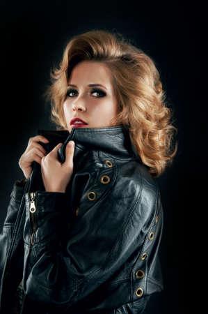 glam rock: Studio portrait of blonde woman in leather biker jacket.Rock style. Stock Photo
