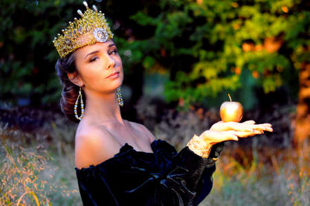 velvet dress: Elegant young woman dressed like queen with a crown holdingan apple