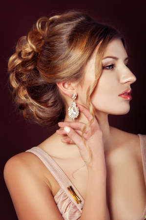 updo: Studio portrait of a beautiful dark blond woman with evening hairdo and makeup wearing precious jewellery