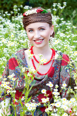 boyar: Happy smiling Russian woman sitting in the field of wild flowers Stock Photo
