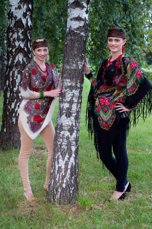 boyar: Two caucasian slavonic women in national costumes standing near the birch tree Stock Photo
