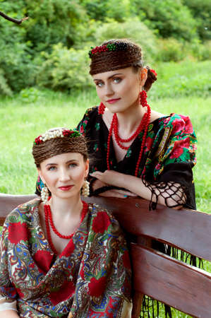 boyar: Two caucasian slavonic women sitting on the wooden bench in the garden