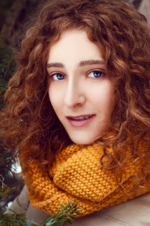 auburn hair: Attractive young woman with curly auburn hair near pine tree with yellow snood and mittens Stock Photo