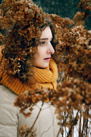 attractive young woman: Attractive young woman with curly hair near dried hydrangea flowers wearing yellow snood Stock Photo