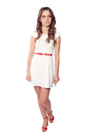 red shoes: Elegant young woman in white dress and red shoes with long curly hair isolated on white