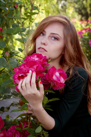 admiring: Beautiful young woman with auburn hair and green eyes admiring roses in the rosary