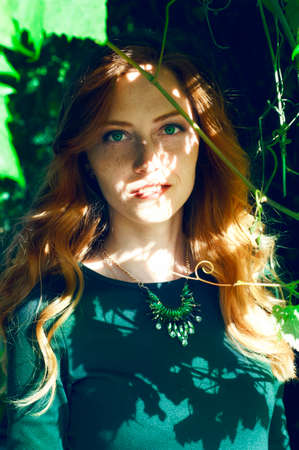 soulful eyes: Beautiful young caucasian woman with auburn hair, freckles and green eyes hiding behind the vine branch