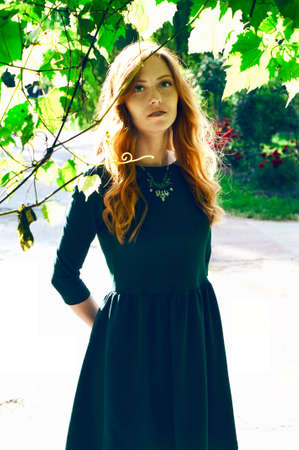 auburn hair: Beautiful young caucasian woman with auburn hair, freckles and green eyes hiding behind the vine branch
