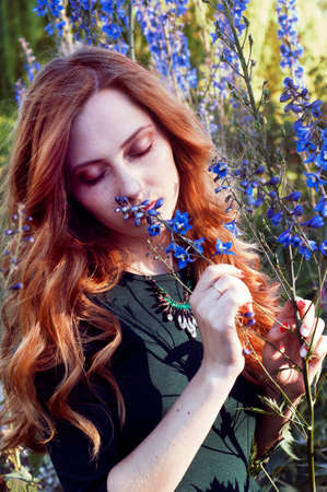 carroty: Sensual redheaded woman in sunset light smelling blue flowers Stock Photo