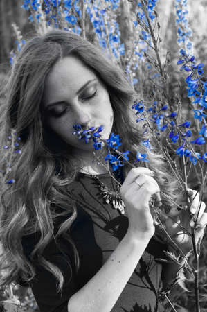 carroty: Sensual redheaded woman in sunset light smelling poisonous aconite blue flowers Stock Photo