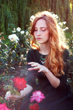 auburn hair: Young woman with auburn hair casting a spell in the rose garden Stock Photo