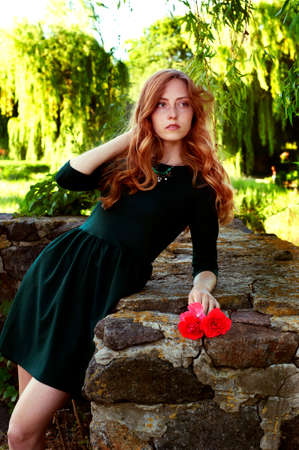 carroty: Young woman with auburn hair in the swamps posing with red flowers