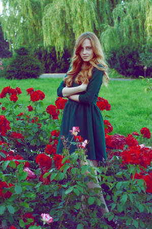 carroty: Mysterious caucasian woman with green eyes and green dress looking at the camera surrounded by scarlet roses