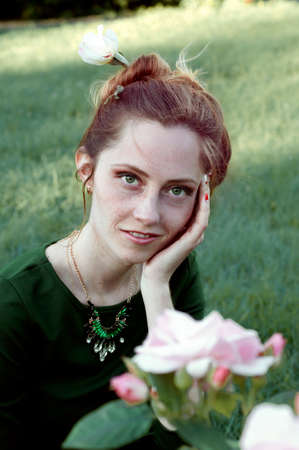 auburn hair: Cheerful caucasian woman with green eyes and green dress sitting outdoors and  looking at the camera and smiling