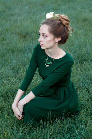 caucasian woman: Cheerful caucasian woman with green eyes and green dress sitting outdoors and  looking away Stock Photo