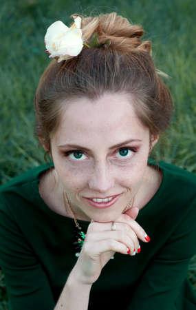 eyes green: Mujer cauc�sica alegre con ojos verdes y vestido verde sientan al aire libre y mirando a la c�mara y sonriendo